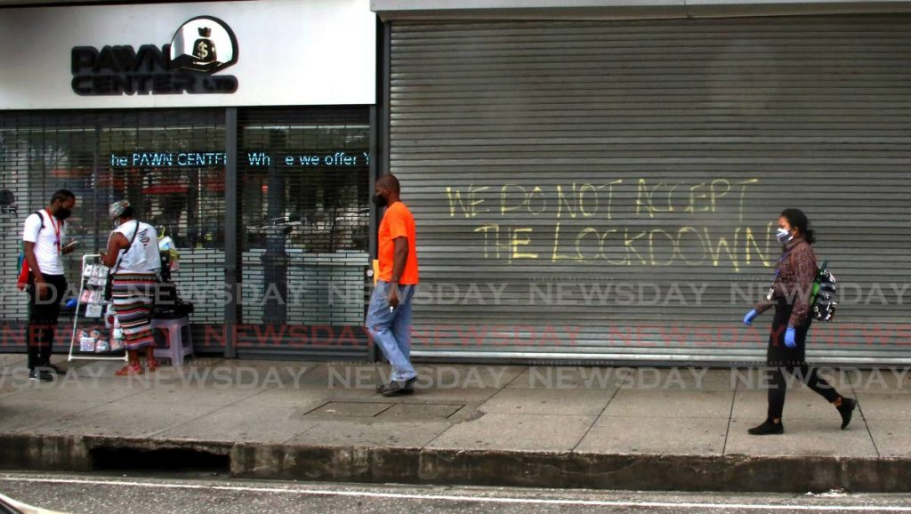 People walk past a sign which says which says 'we do not accept lockdown' painted on the security barrier of a business place on lower Frederick St, Port of Spain. - SUREASH CHOLAI