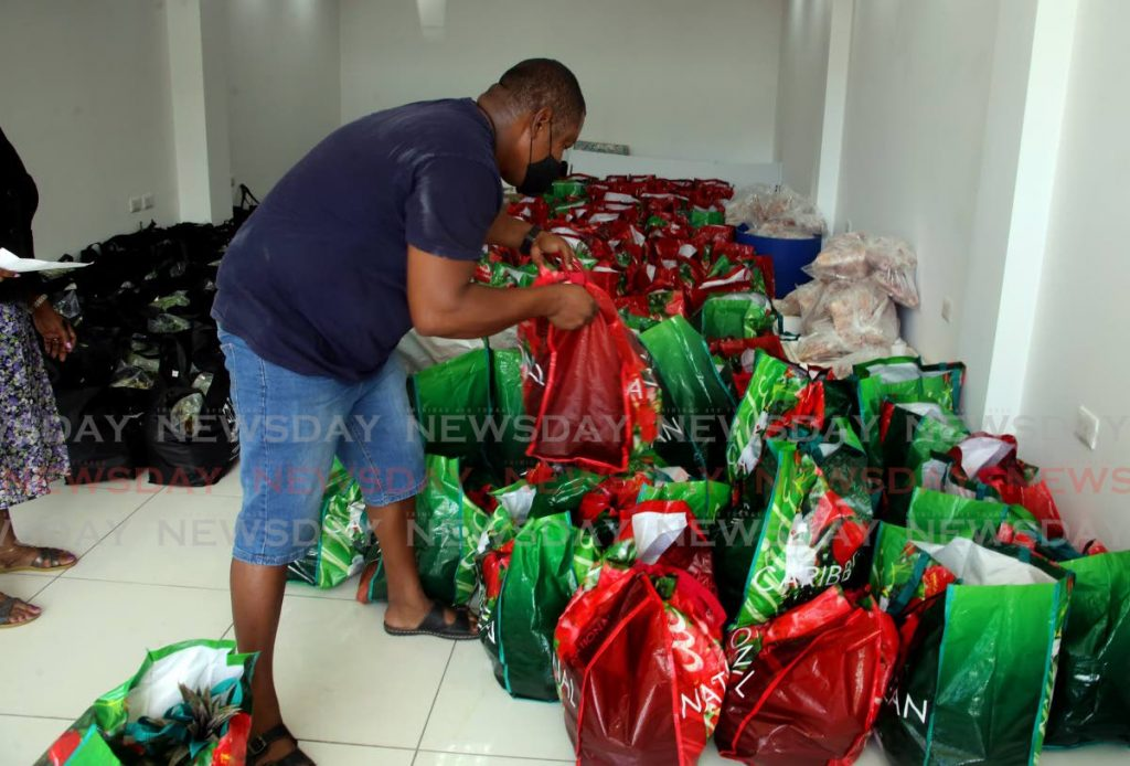 A man sorts through food basket hampers at the constitutency office of St Ann's East MP. Some 25,000 hampers were distributed by the government across all 41 constituencies.  - SUREASH CHOLAI