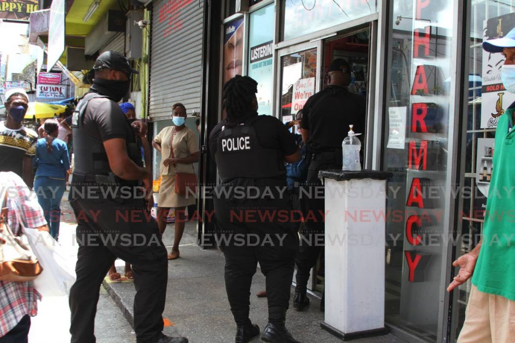 Police enter a store on Charlotte St, Port of Spain on May 12 to ensure everyone adheres to covid19 restrictions and protocols - Marvin Hamilton
