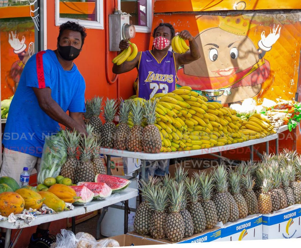 Devanan Boodram, right, holds some bananas for sale at his fruit and vegetables stall in Scarborough on Monday. Photo by David Reid-