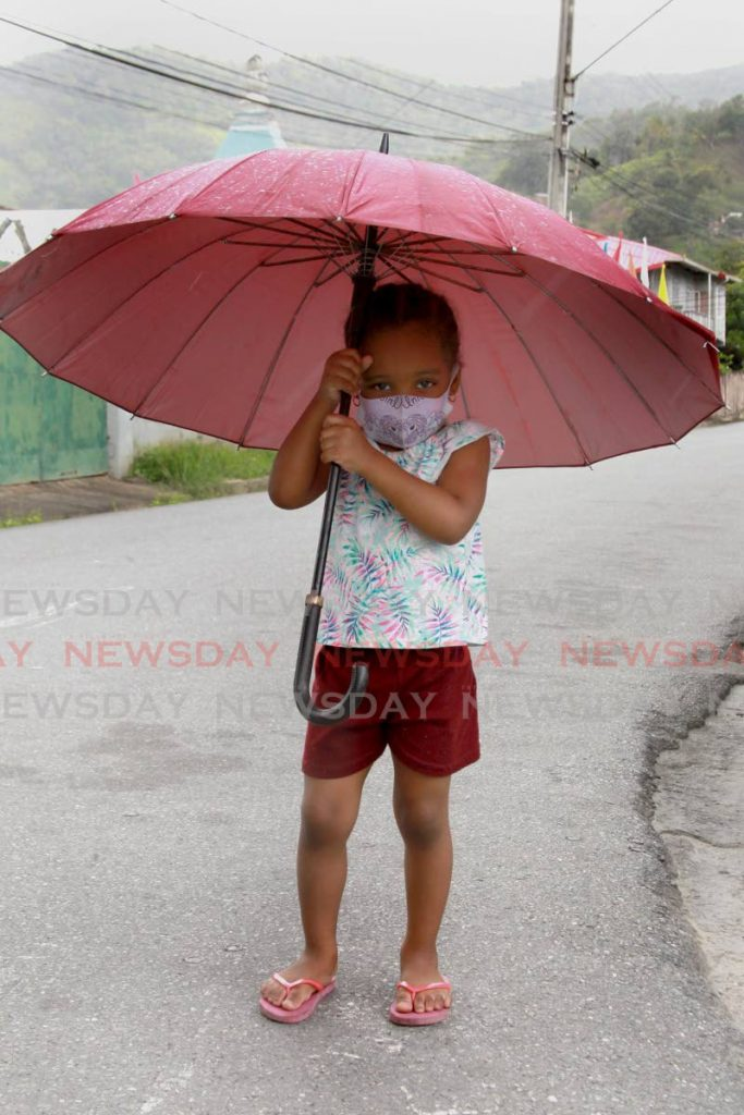 UNDER MY 'BROLLY: Azari Hamilton, three, holds her umbrella as she made her way to a parlour in St Lucien Road, Diego Martin. She was accompanied by her father who moved out of the way to allow his daughter the photographic spotlight. PHOTO BY ROGER JACOB  -