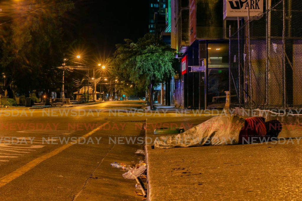 A homeless woman sleeps alone on the pavement near the corner of Frederick Street and Independence Square, in Port of Spain on Sunday night. - Photo by Jeff Mayers