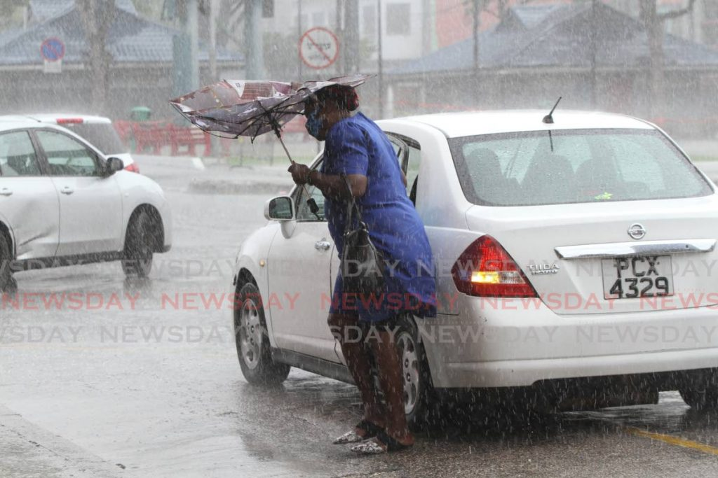 A woman struggles with her umbrella as she exits a car on Independence Square, Port of Spain during heavy rainfall in May. -
