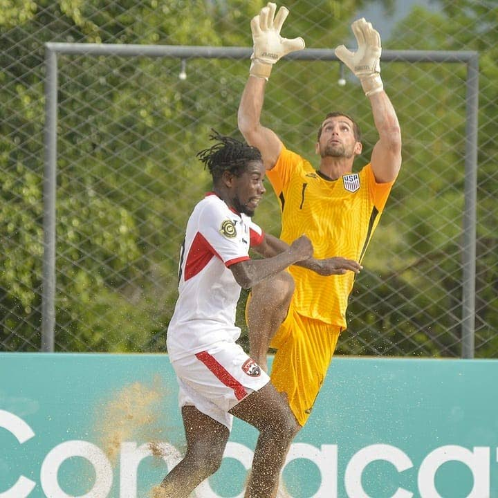 TT beach soccer player Dominic McDougall challenges US goalkeeper Christopher Toth for the ball during Tuesday's match in the Concacaf Beach Soccer Championships in Alajuela, Costa Rica. US won the game 5-2. PHOTO COURTESY TT FOOTBALL ASSOCIATION. -