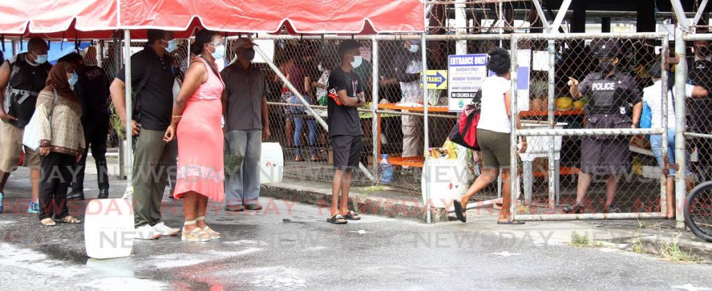 A police officer controls the amount of people entering the Marabella market on Sunday morning.   - Angelo Marcelle