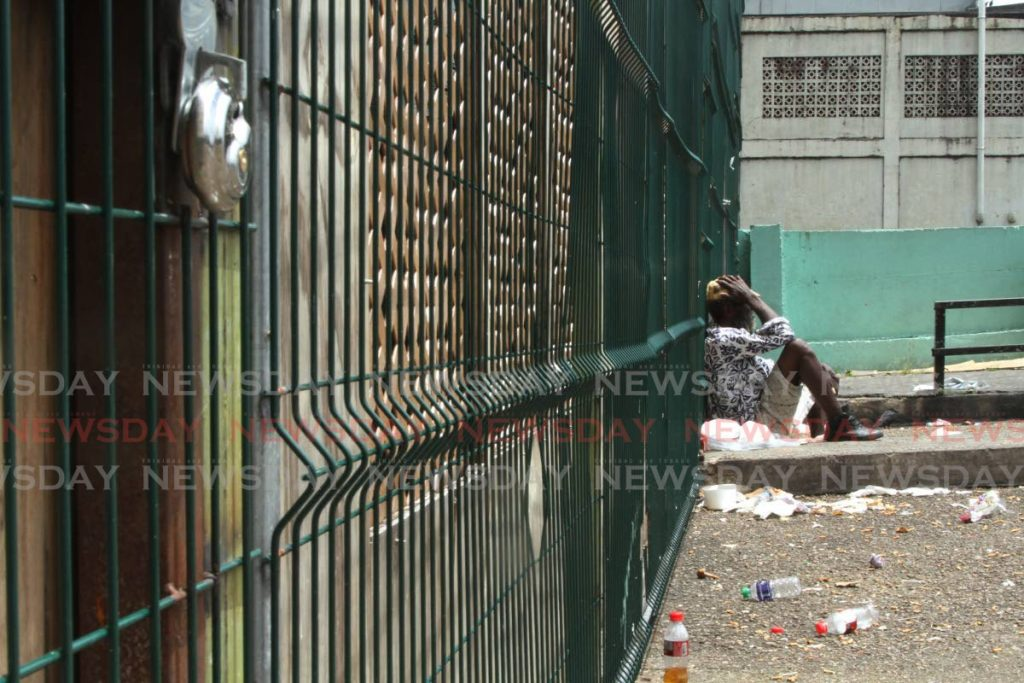 STILL LOCKED: A man sits outside the locked temporary shelter at Riverside Plaza in East Port of Spain on Sunday. The mayor has refused to open the shelter since the NGO who will manage its use has an ongoing court matter with the corporation. Photo by Marvin Hamilton