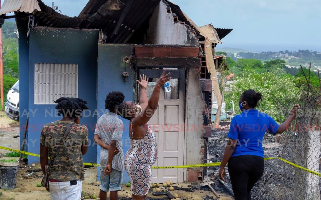 SORROW: Margaret Seaforth gestures to the heavens as she and other relatives stand outside her home in Union Village Street, Tobago which was gutted by fire. PHOTO BY DAVID REID -