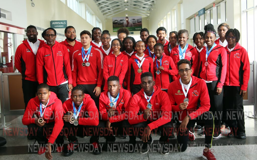 In this April 24 file photo, members of the TT swimteam who bagged 24 medals at the Carifta games pose for a group photo when they arrived at the Piarco International Airport Photo by Sureash Cholai