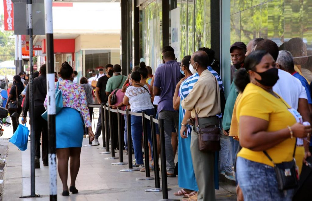 In this file photo, people wait in line on the pavement outside a bank in Port of Spain. Minister in the Ministry of Public Administration and Digital Transformation Hassel Bacchus a lack of trust in the local systems means the same people who purchase items online from foreign sites, would rather stand in line to pay for goods and services in TT. - Sureash Cholai