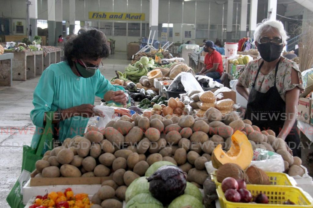 In this file photo, a customer selects her potatoes from a stall at the San Fernando Market. -Photo by Ayanna Kinsale