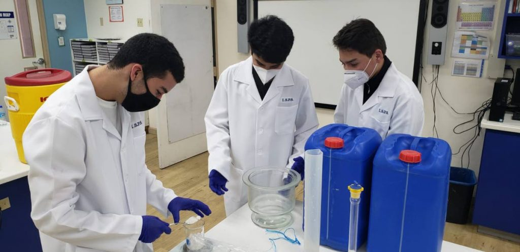 Students at ISPS make hand sanitiser in the school science lab. -