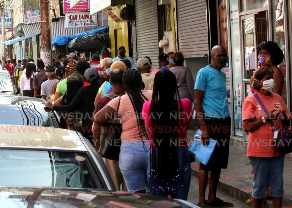 Scores of people wait in line for an opportunity to get into Pennywise's Charlotte Street branch in Port of Spain on Tuesday. The street is simultaneously packed with cars. - SUREASH CHOLAI