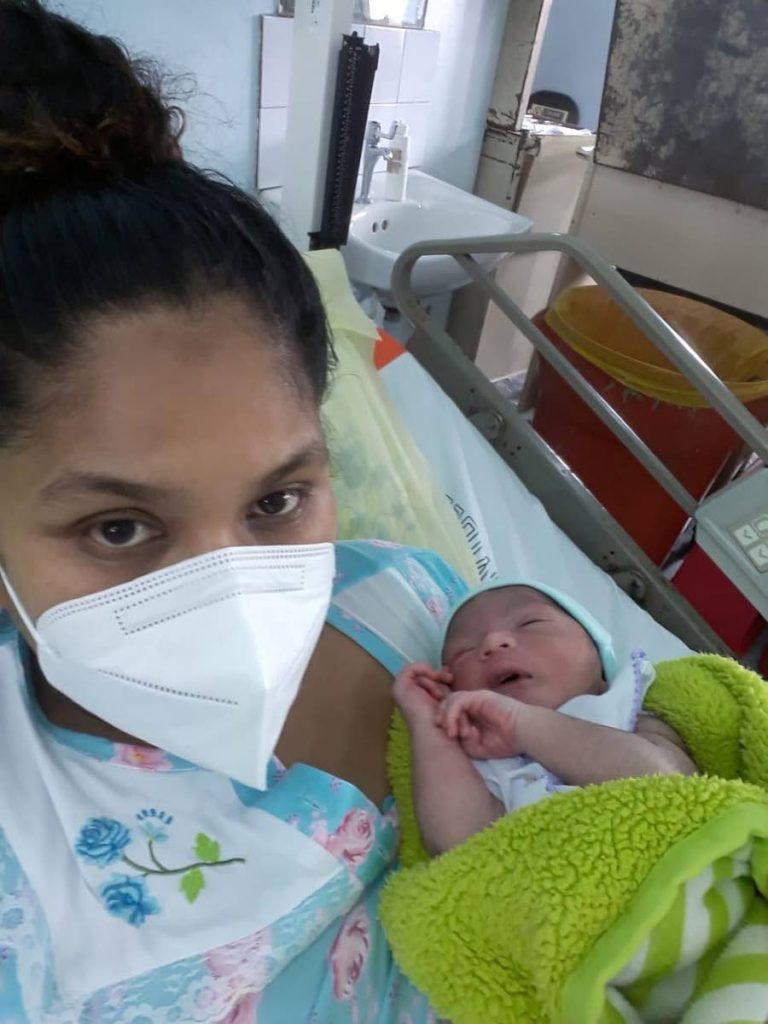 MIRACLE: Christine Arjoon and her, as yet unamed, newborn baby boy at the San Fernando General Hospital on Tuesday. Arjoon gave birth in a car at the side of the road in Otaheite after being turned away from the Point Fortin Hospital around 4 am on Tuesday morning. -