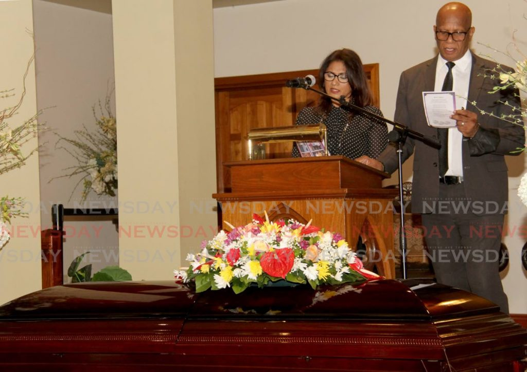 """Michelle Mohamed-De Freitas, daughter of Lennox """"Bobby"""" Sylvanus Mohamed, San Fernando Mayor Juna Regrello lead the small congregation in song at Mohamed's funeral at Guides Funeral Home, Coffee Street, San Fernando on Tuesday. - AYANNA KINSALE"""