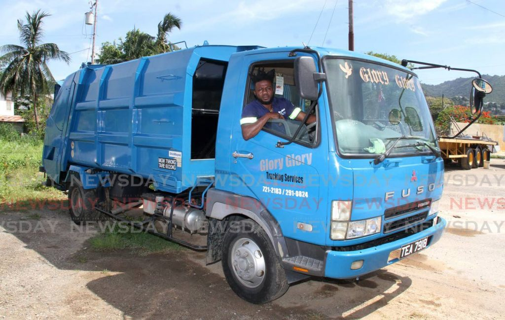 Glory Glory Transport Services managing director Ronald Musgrave sits in the company's newest garbage truck compactor. - Angelo Marcelle