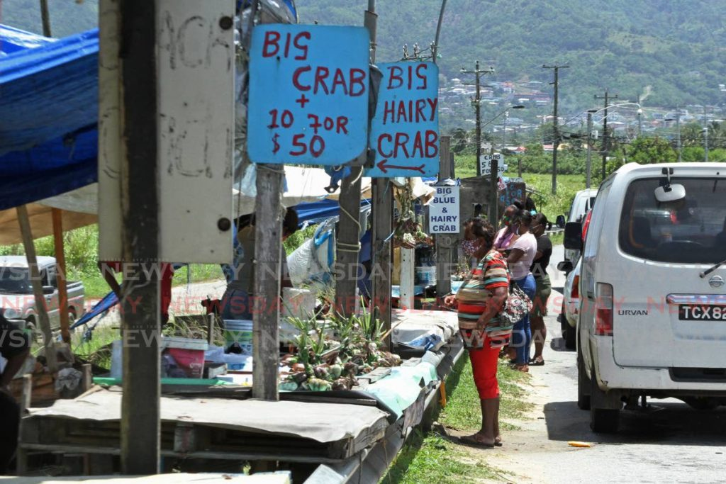 File photo: Customers made their purchases from crab vendors on Wednesday near the bridge on the Southern Main Road in Caroni. Vendors said police told them they could not sell and they had to pack up and leave. Photo by Marvin Hamilton