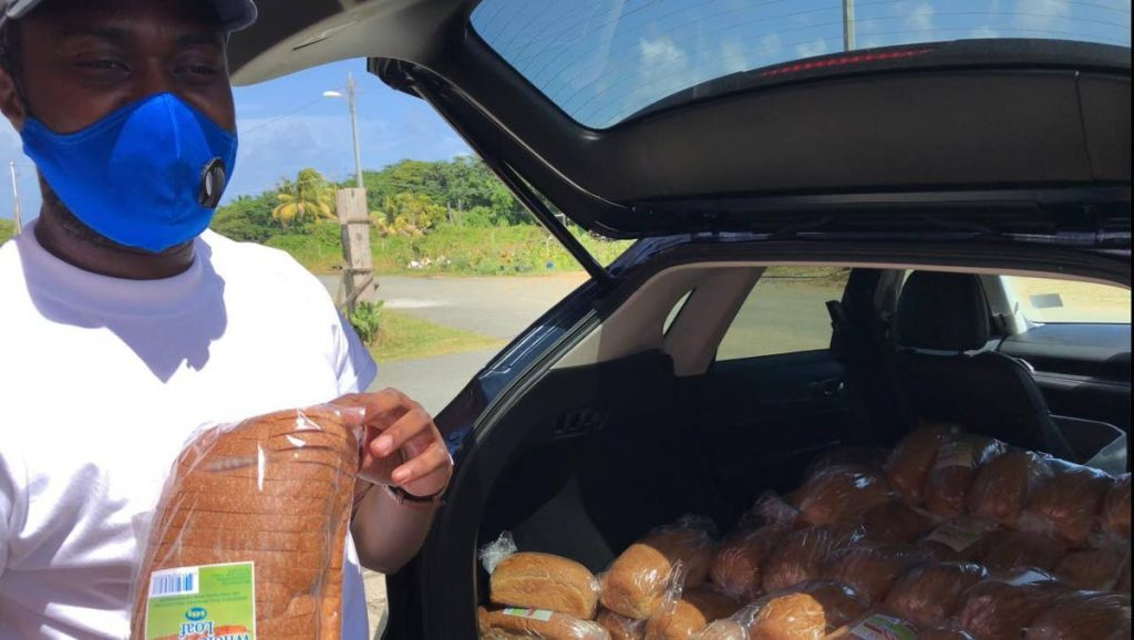Progressive Democratic Patriots (PDP) deputy leader Farley Augustine with loaves of bread to distribute to people struggling amid the pandemic.  -