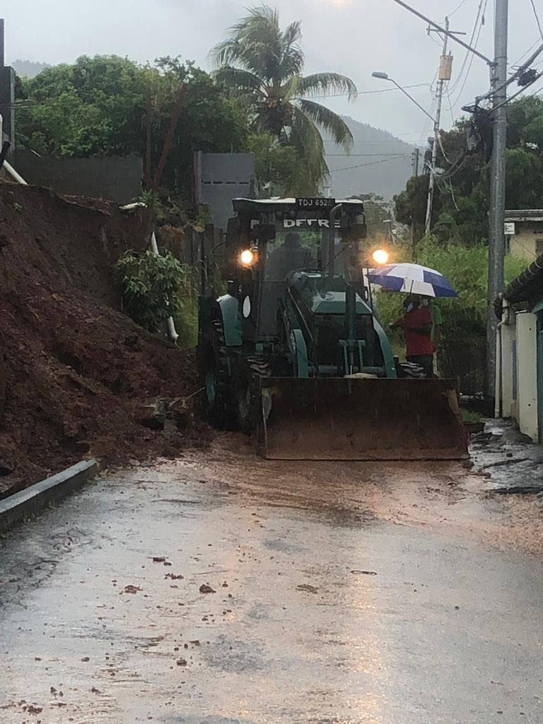 A tractor removes debris from Maniram Trace, Five Rivers after a retaining wall collapsed due to heavy rainfall in the area on Friday morning - Kwasi Robinson