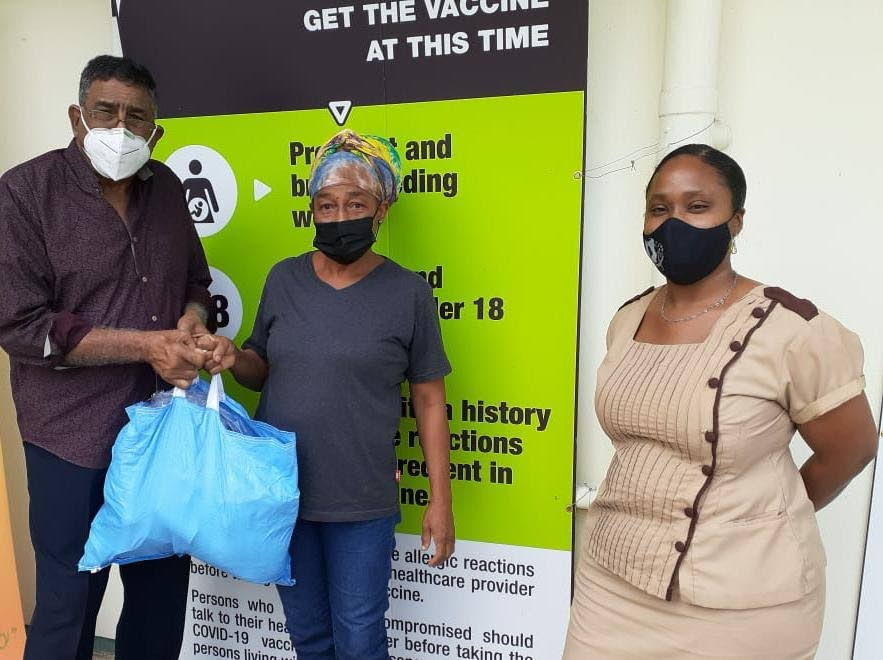 Joan Bethelmy receives a hamper from councillor Terry Rondon at the Toco Health Centre, Toco. At right is nurse Penny Ramlachan. -