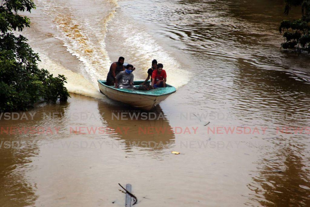 Fishermen head up the Caroni River on Saturday. - SUREASH CHOLAI