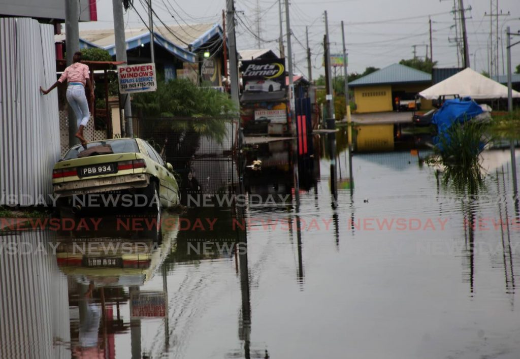 To avoid flood water a young woman chose to walk on top of car to get to her home at Bamboo Boulevard in Bamboo No 3 Valsayn. - SUREASH CHOLAI