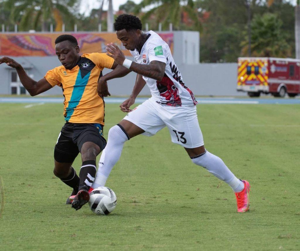 Trinidad and Tobago's Keston Julien, right, runs at a Bahamas player in a Concacaf World Cup qualifier on Saturday at the Thomas Robinson Stadium, Nassau, Bahamas.  Photo courtesy TTFA