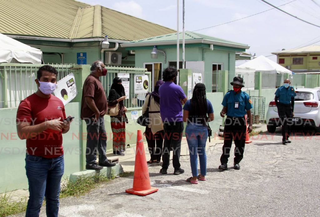 People wait outside the Barataria Health Centre on Monday before being allowed in to receive their covid19 vaccines. - ROGER JACOB