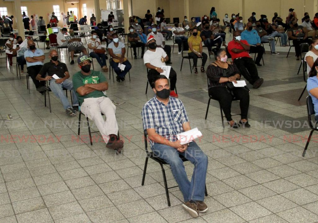 Supermarket workers wait to be vaccinated at Centre Pointe Mall in Chaguanas on Tuesday. - Photo by Ayanna Kinsale