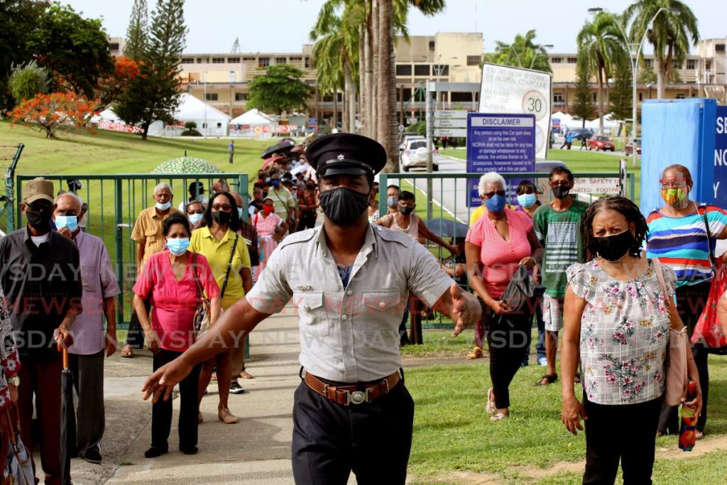 MOVE ALONG: This policeman had his hands full in trying to control the crowds which gathered early on Wednesday morning outside the St Joseph Enhanced Health Centre in Mt Hope as they tried to get their covid19 vaccine shot. PHOTO BY SUREASH CHOLAI -