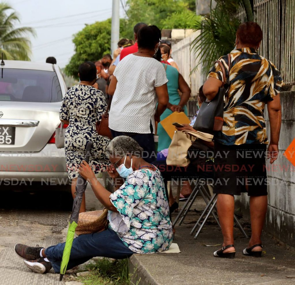 An elderly woman sittng on the pavement outside the San Juan Health Centre waiting her turn for the covid19 vaccine shot. - SUREASH CHOLAI