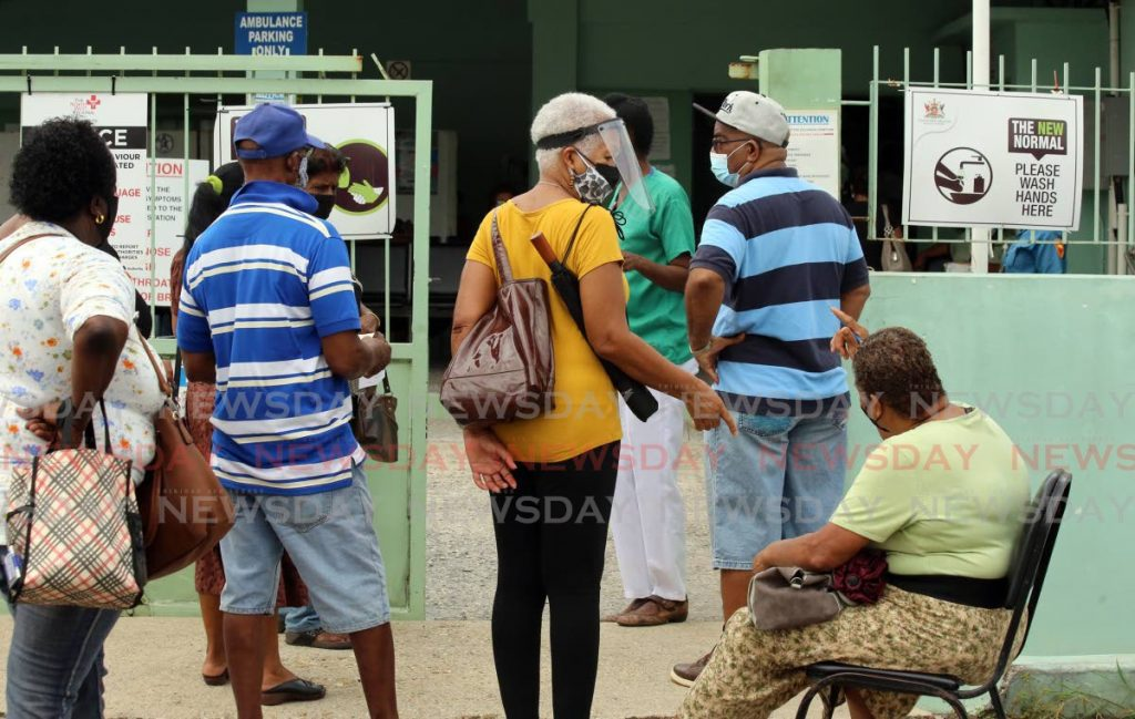 A combination of people trying to get the covid 19 vaccine shot and regular clinic goers waiting outside Barataria Health Centre. - Photo by Sureash Cholai