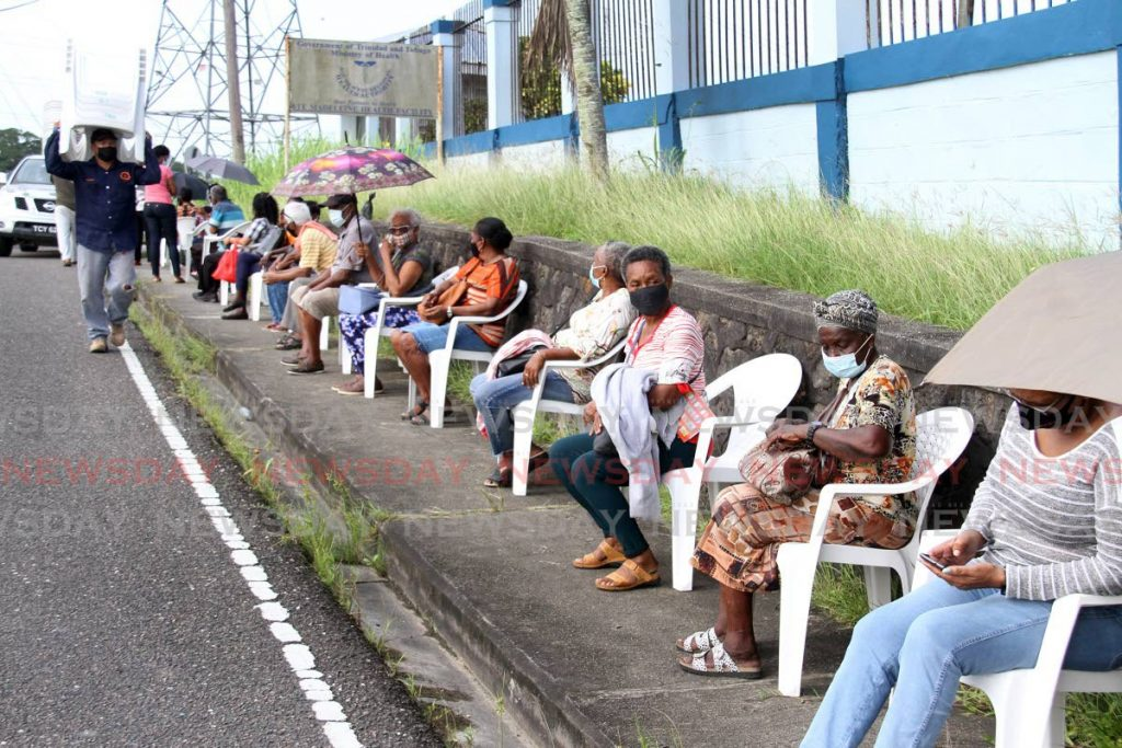 Senior citizens sit on chairs donated by Bilda Boyz Construction Services outside the Ste Madeleine Health Centre, Manahambre Road on Friday morning. Photo by - Angelo Marcelle