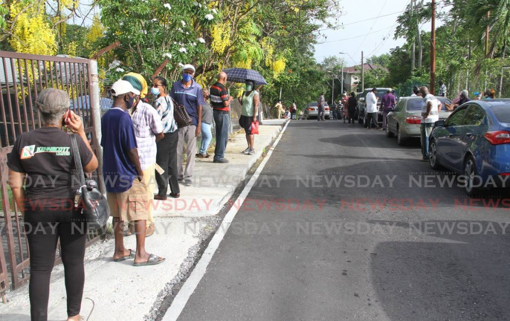 Senior citizens stand on both sides of Zaida Lane outside the La Romaine Health Centre on Friday morning. People came as early as 5am to get their 1st covid19 vaccine.  Photo by - Angelo Marcelle
