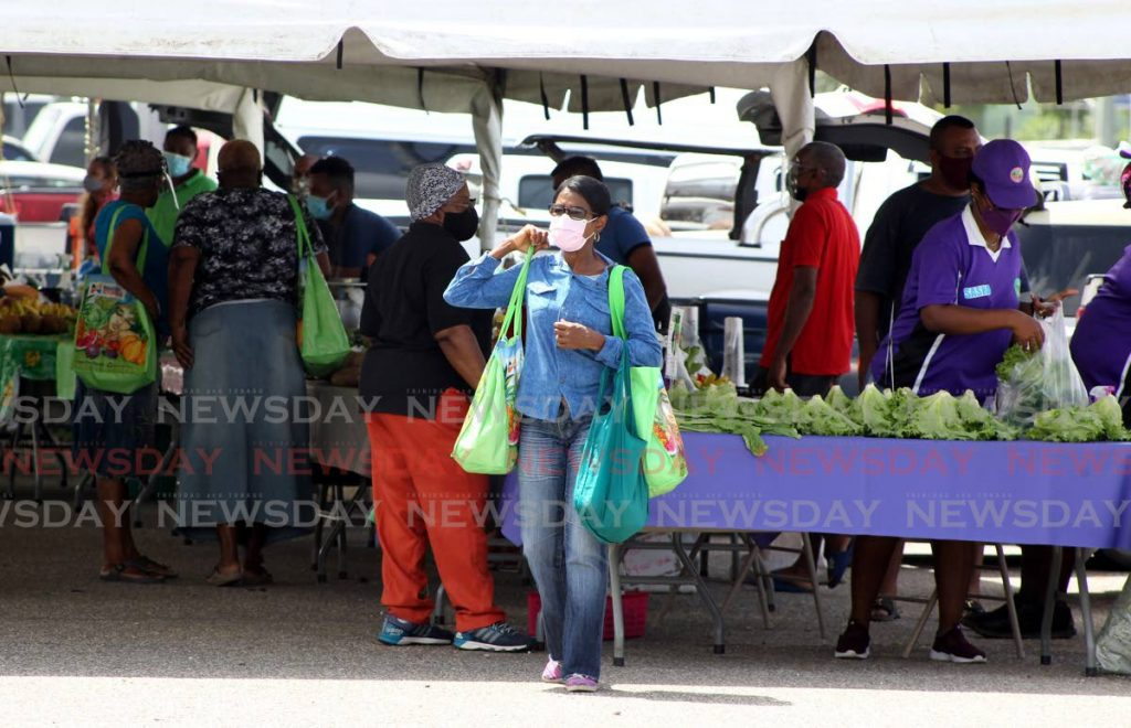 People at the Namdevco farmers' market at the Queen's Park Savannah on June 12. -Photo by Roger Jacob
