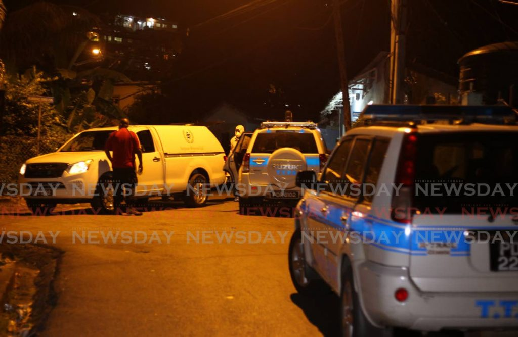 Undertakers and police at the scene of the murder ay Douglas Trace, Upper Simeon Road, Petit Valley on Sunday night. - ROGER JACOB