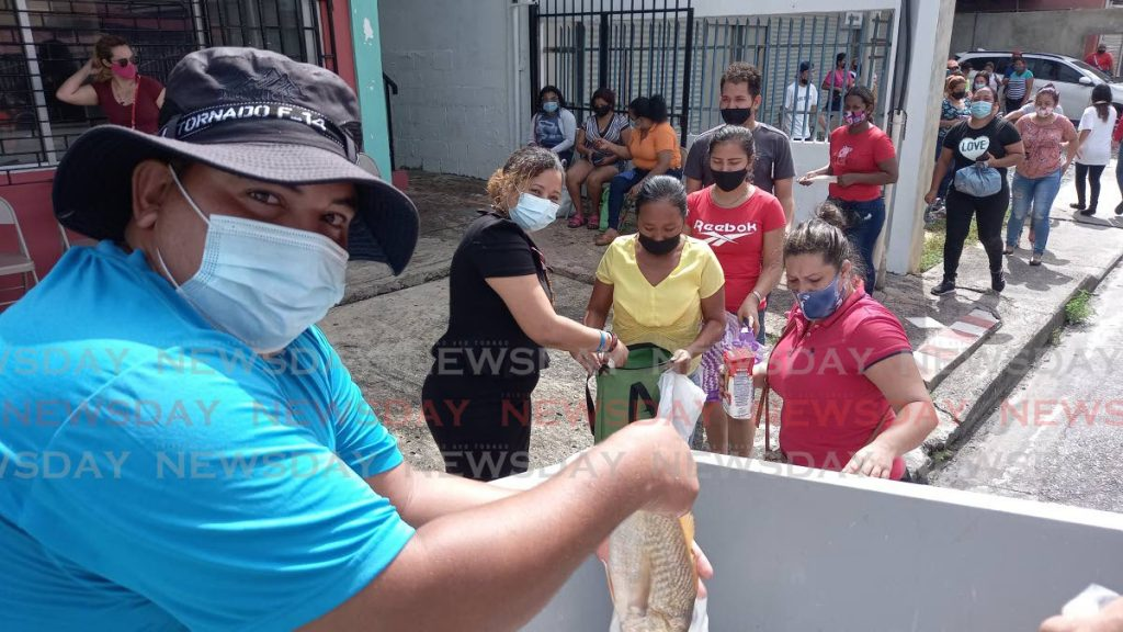 Carlos Hernandez during distributes free fish in front of the La Casita building on Farfan St in Arima. More than 100 people were able to receive a bag of cro-cro fish and a cornmeal. - Grevic Alvarado