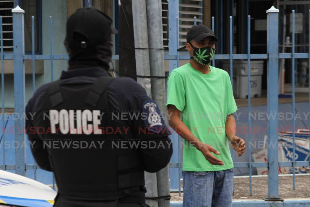 Police question a man outside the St James Police Station after he was seen walking along the Western Main Road, St James on Saturday during curfew hours. - Photo by Marvin Hamilton
