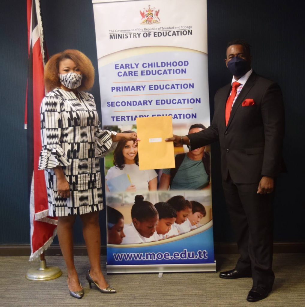 Education Minister Dr Nyan Gadsby-Dolly presents the instrument of appointment to chairman of the Niherst board Dr Andrew Hunte on Friday. - Photo courtesy Ministry of Education