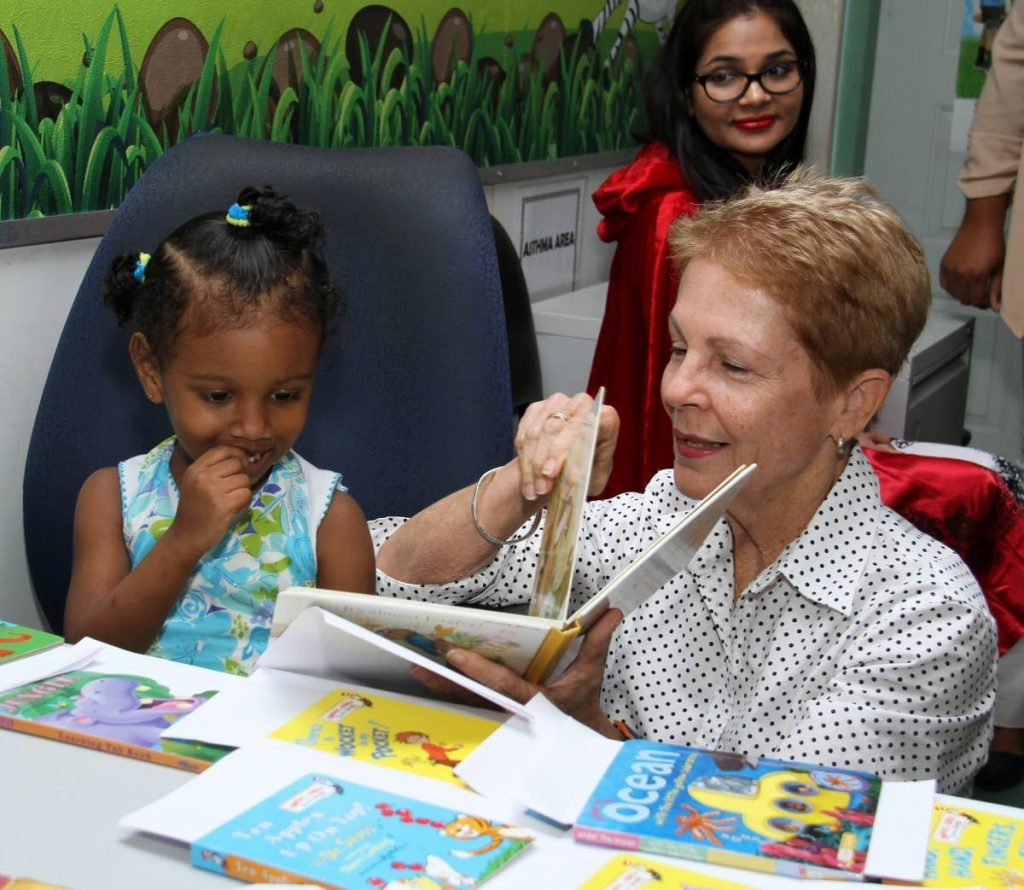 Let's Read co-founder Suzette Cadiz reads to a girl at one of the NGO's school libraries. Photo courtesy Suzette Cadiz -