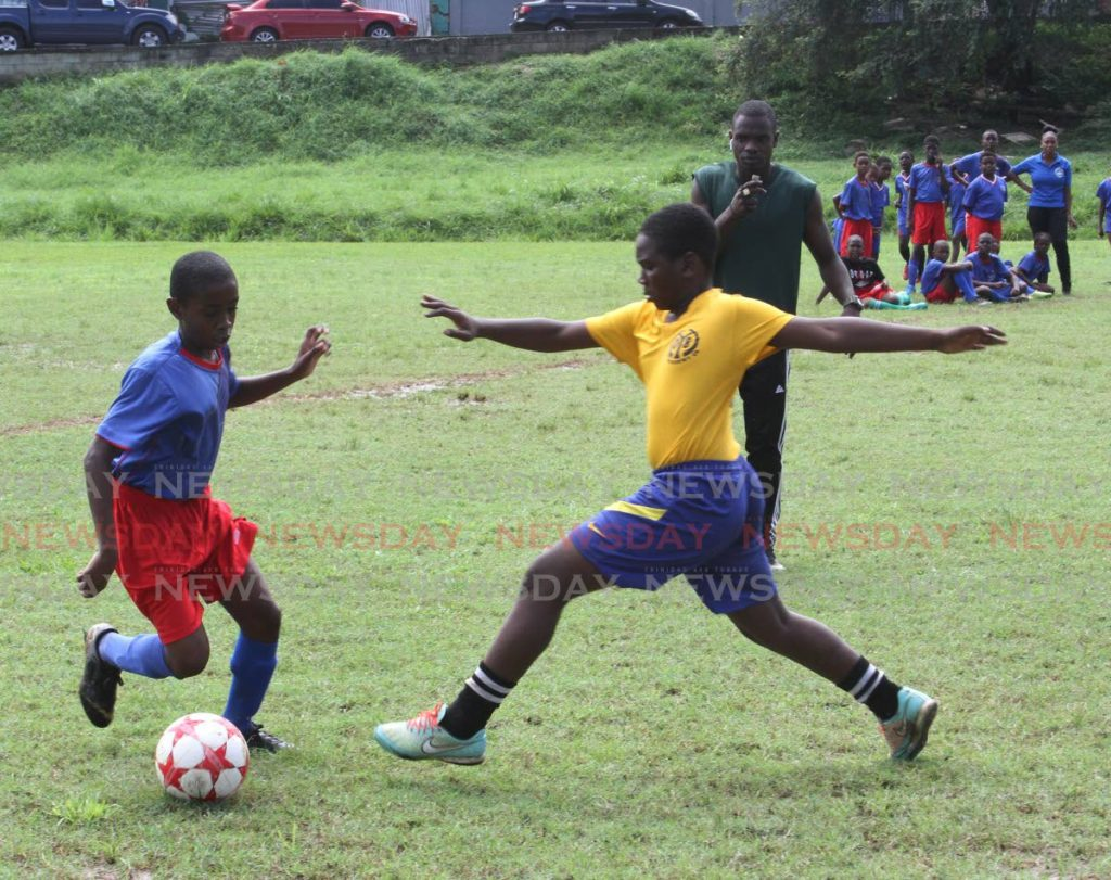 In this Nov 22,2019 file photo,A St. Dominic's Rc Primary School player, left, dribbles past a player from the Morvant Football Academy, at the TTPS North Eastern Division Morvant  Community Police 3rd annual primary school football competition, held at the Morvant Recreation Ground. On Monday, a statement issued by the FIFA announced an MoU between FIFA and Caricom which 'focuses on several key areas of collaboration, in particular the implementation of a football programme in the physical education curricula in primary schools in the Caricom region.' - Angelo Marcelle