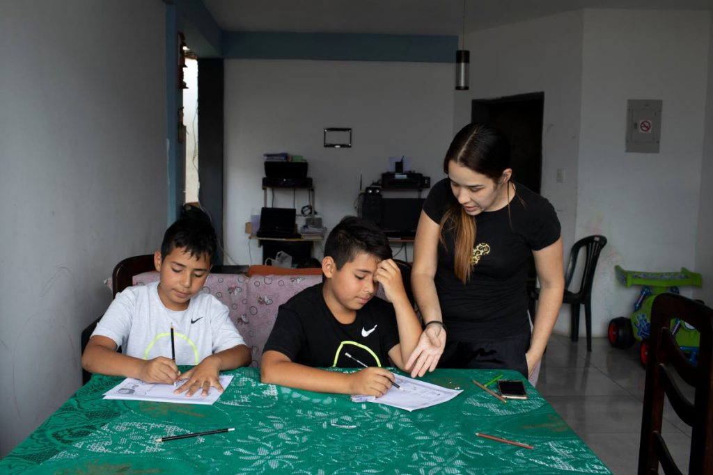In this file photo, Maria Figueroa explains homework to her son Fabian, centre, as her other son Sebastian works on his at their home in the Catia slum of Caracas, Venezuela. - AP PHOTO