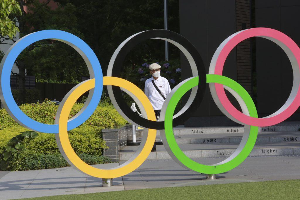 In this photo a man walks past the Olympic rings in Tokyo, (AP Photo/Koji Sasahara)