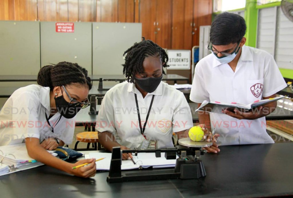 In this February 2021 file photo, Tunapuna Secondary School form five students Rayanna Pantin, Jada Mayers and Vivek Ragbir conduct a physics experiment in the school laboratory. The government has said it would guide students into areas that align with the national development agenda, but that agenda has not been clearly articulated. - ROGER JACOB
