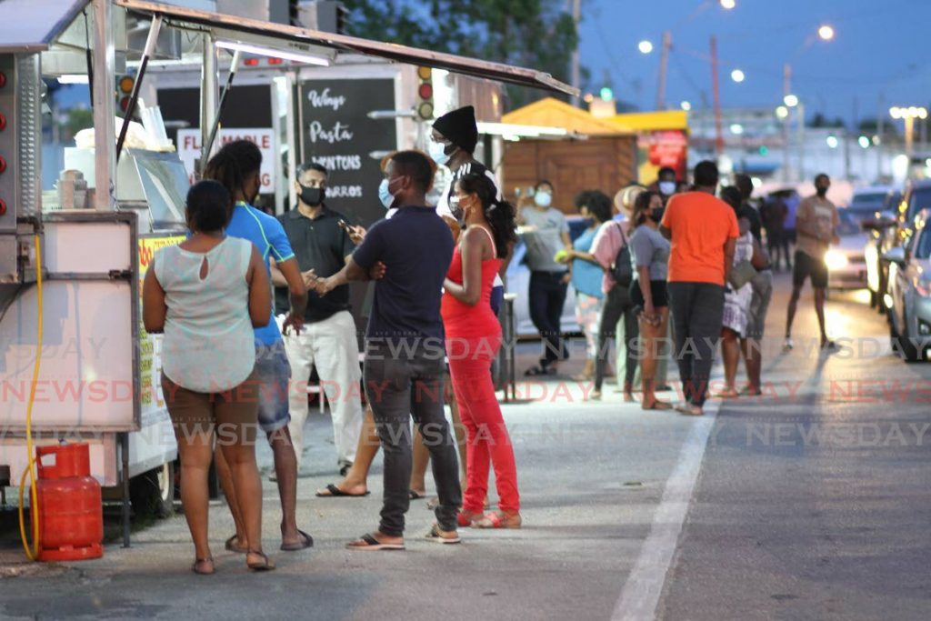 FILE PHOTO: Customers wait for food from vendors at Cross Crossing, San Fernando, on May 3. After initially saying no, Mayor Junia Regrello has agreed to let food vendors operate in the area again from Monday between 2 pm and 8 pm daily. -
