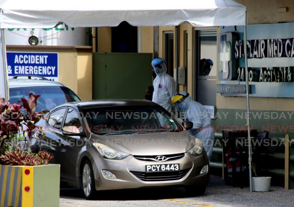 A lab techinician takes a sample for a covid19 test from a member of the public in a drive-through facility at St Clair Medical Centre, St Clair on May 15. A private covid19 test can save an employee ten days' pay or ten days' performance. File photo/Sureash Cholai -