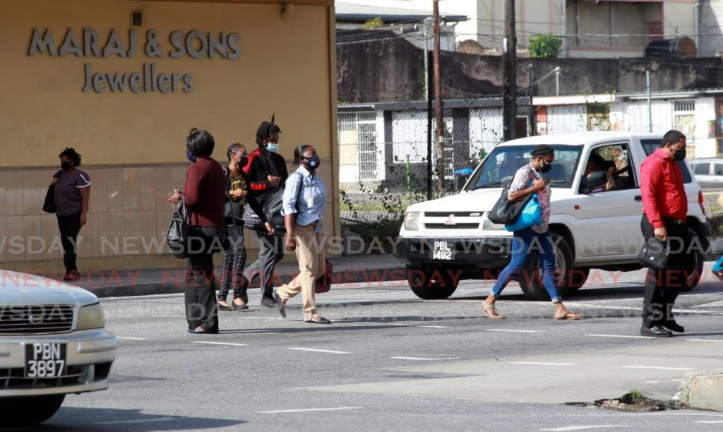Pedestrians head to City Gate across South Quay in Port of Spain. - File photo