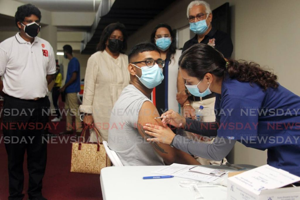 Rayon George, an employee of Carib Glass Works, receives his Sinopharm jab from Anita Mohommed during the mass vaccination drive for workers in the manufacturing sector at the Divali Nagar site, Chaguanas on June 6. Health Minister Terrance Deyalsingh, Trade Minister Paula Gopee-Scoon, Manufacturers Association president Trisha Coosal and Medical Association president Dr Vishi Beharry look on.  - Photo by Lincoln Holder
