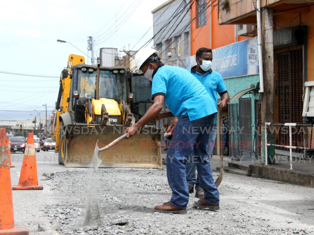 WASA workers repave an area of High Street, San Fernando after repairing an underground main in June. Government ministers Pennelope Beckles, head of the cabinet transformation committee on WASA, and Public Utilities Minister Marvin Gonzales meet with the WASA board on Saturday. - PHOTO BY AYANNA KINSALE