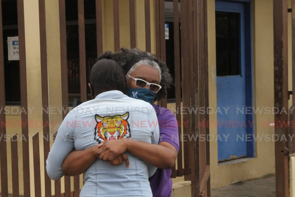 Shannon Whyte's mother, Veronica, tiger print shirt, is comforted by a relative outside Forensic Science Centre, St James, on Friday. Photo by Marvin Hamilton