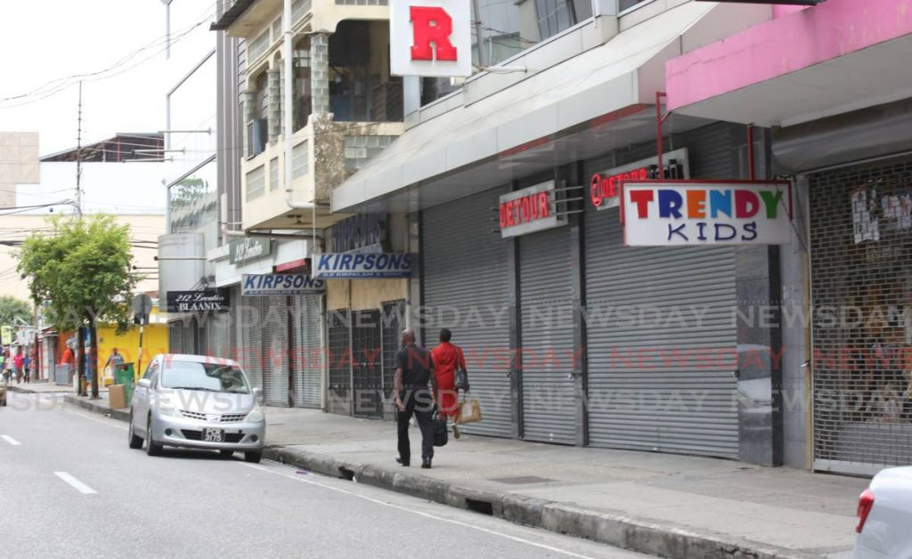 Pedestrians walks past stores that remain closed on Frederick Street, Port of Spain. Many businesses may remain permanently closed even when covid19 restrictions are lifted leading to job loss among low-income workers. - Photo by Sureash Cholai